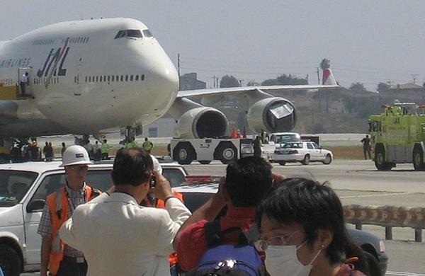 멀리 일본항공 B747 항공기 엔진에 뭔가가 걸려있다.