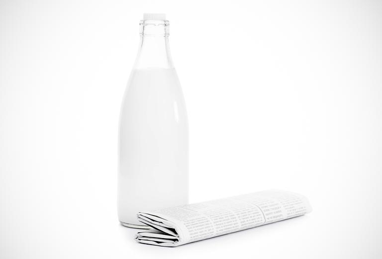 흰 우유가 들어있는 유리병과 신문